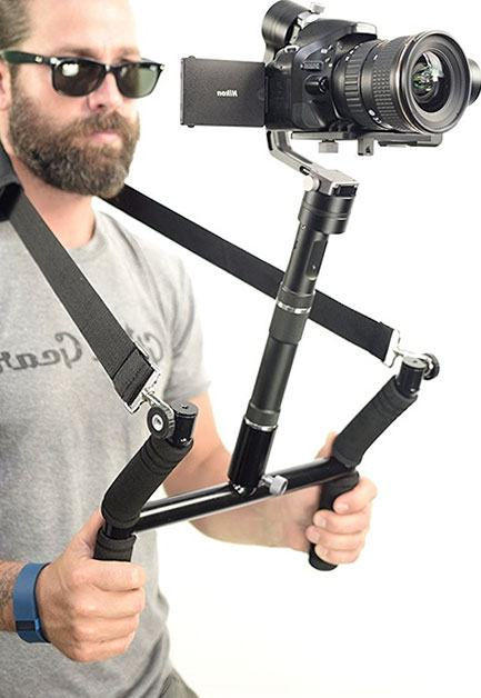 Man Holding a DSLR camera mounted on a chest stabilizer