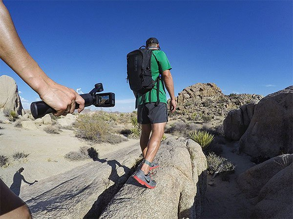 Man holding a gopro karma grip gimbal while walking on rocks